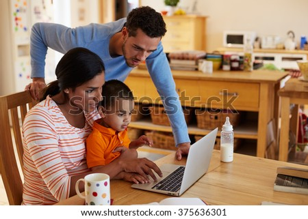Family In Kitchen Looking At Laptop Together - stock photo