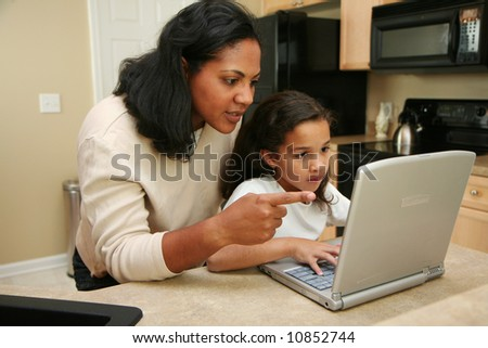 Family in kitchen on the computer