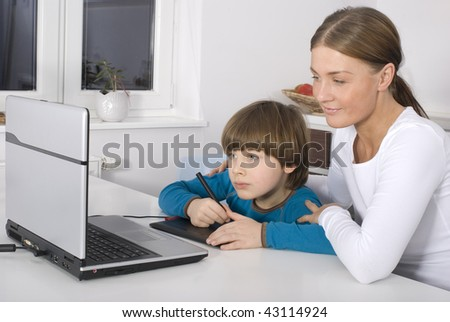 Family in kitchen with laptop - stock photo