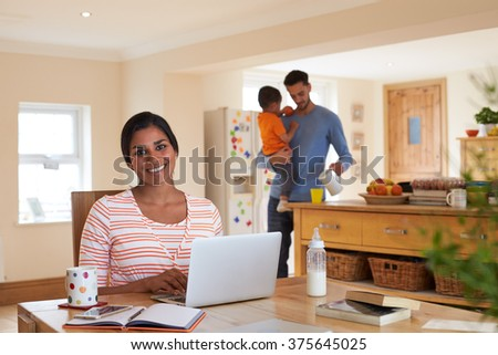 Family In Kitchen With Mother Using Laptop At Table - stock photo