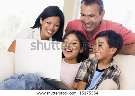 Family in living room with laptop smiling - stock photo