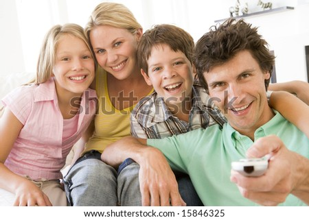 Family in living room with remote control smiling - stock photo