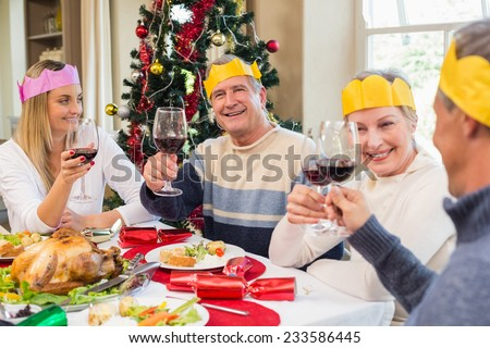 Family in party hat toasting at christmas dinner at home in the living room - stock photo