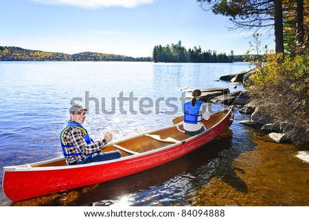 Family in red canoe near rocky shore of Lake of Two Rivers, Ontario, Canada - stock photo