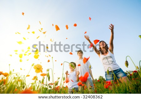 family in red poppy field - stock photo