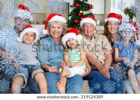 Family in Santa hats celebrating Christmas against snowflake frame - stock photo