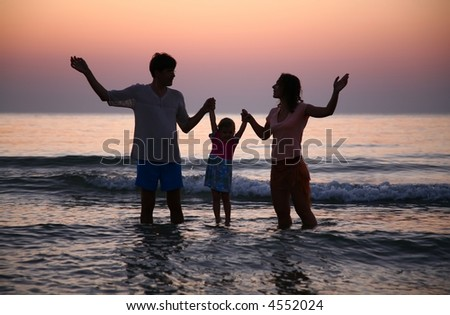 Family in sea on sunset