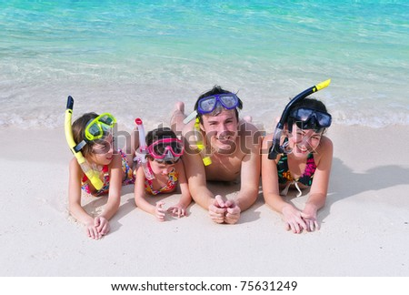 Family in snorkels on tropical beach - stock photo