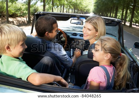 family in sports car - stock photo