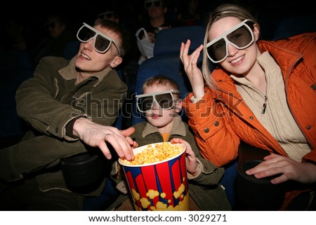 family in stereo cinema. focus on popcorn - stock photo