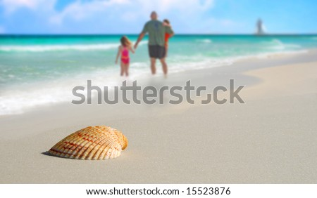 Family in surf by Pretty seashell on beach with sailboat in distance - stock photo