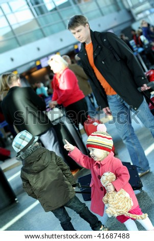 Family in the airport. Cute girl showing the right way. - stock photo