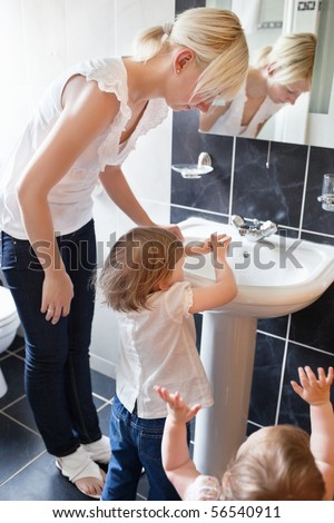 Family in the bathroom washing hands - stock photo