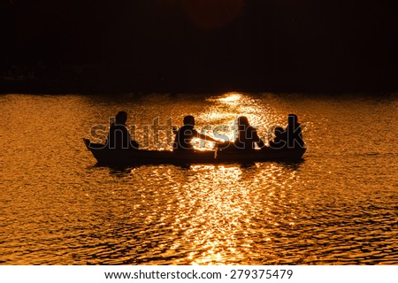 Family in the boat on the lake in sunset glow. Silhouettes. Harmony with nature idea.  Aged photo.  - stock photo