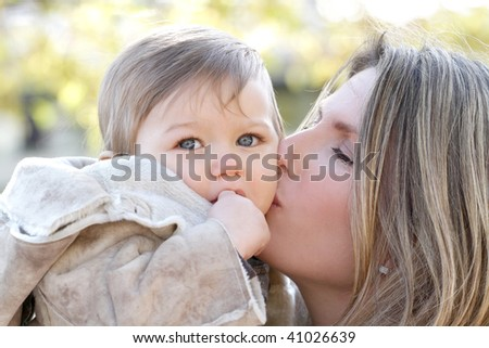 Family in the fall: mother and baby son outdoors, city street setting - stock photo