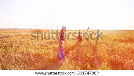 family in the field at the  sunset - stock photo