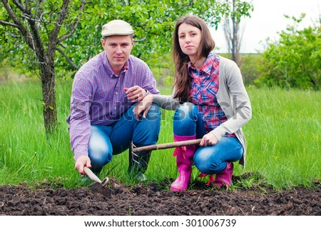 Family in the Garden resting after work. Woman and Man  Working in the Garden together. Healthy Lifestyle - stock photo