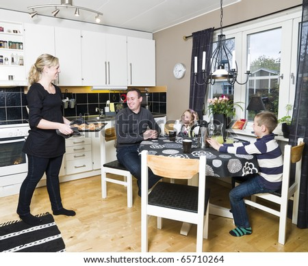 Family in the kichen with baked cookies - stock photo