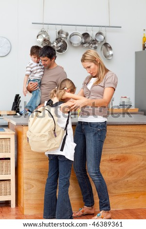 Family in the kitchen before going to school after breakfast - stock photo