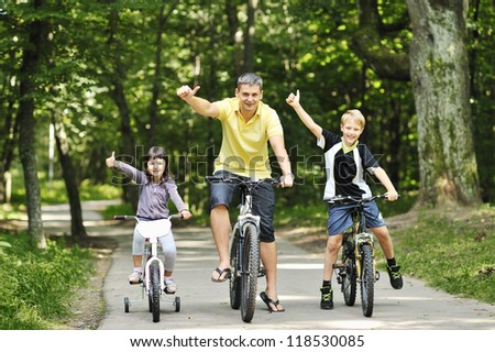 Family in the park on bicycles - stock photo