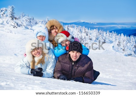 Family in winter clothing lie on the mountainous hill - stock photo