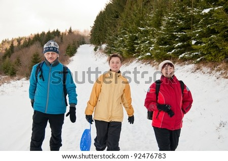 Family in winter together walking in snow - stock photo