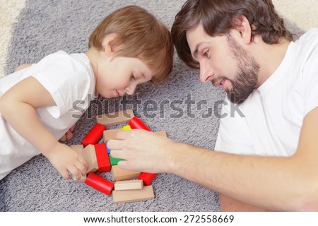 Family interaction. Young handsome father and cute son play building kit lying on a carpet in children room - stock photo