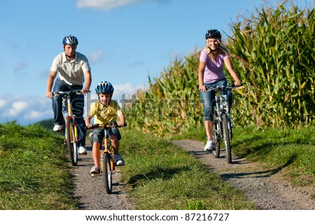 Family is cycling in summer - here mother, father and son