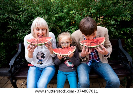 Family is eating a watermelon together in the park. Sitting on the stone and smiling. Looking for each other.