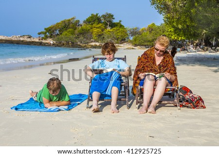 family is enjoying the sun and relaxing and reading books at the beautiful beach
