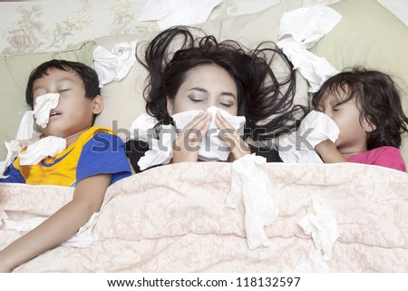 Family is lying on a bed due to flu in winter
