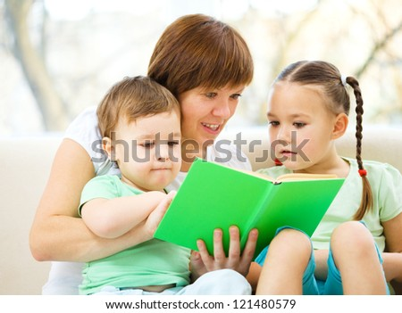 Family is reading book while sitting on a couch, indoor shoot - stock photo