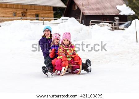 Family is sledding down the snowy slope. Family enjoying active vacation on ski sledge. - stock photo