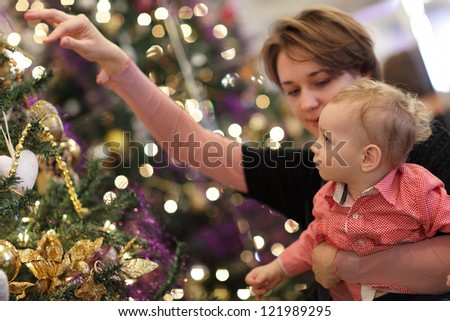 Family is spending time by Christmas tree at home - stock photo