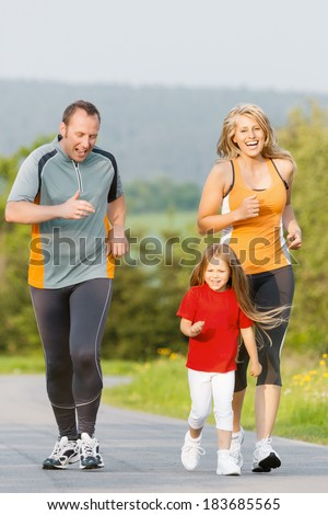 Family jogging for sport for fitness outdoors with the kids - stock photo