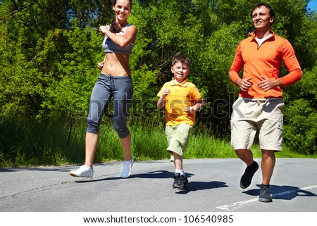 Family jogging in the open air enjoying summer vacations - stock photo