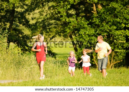 Family  jogging with two little daughters - stock photo