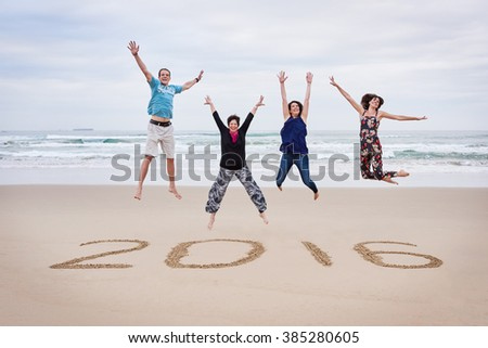 Family jumping on the beach together for 2016
