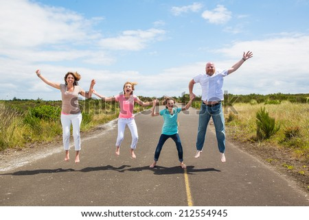 Family jumping together on the road - stock photo
