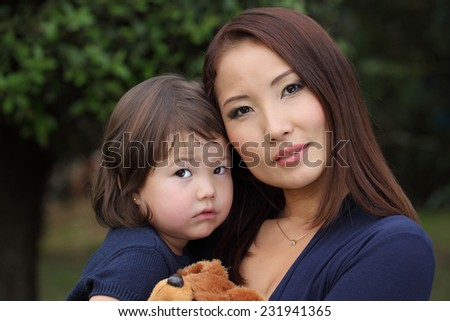 Family Koreans. Mother and daughter. Mother with her baby in her arms. Mom and baby Asian appearance. - stock photo