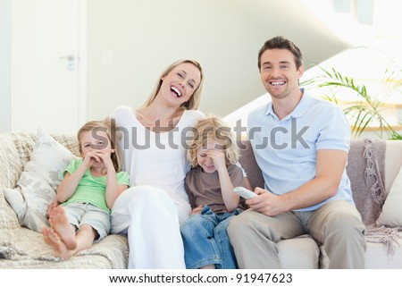 Family laughing on the sofa together - stock photo