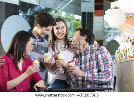 Family Laughing While Having Ice Creams In Parlor - stock photo