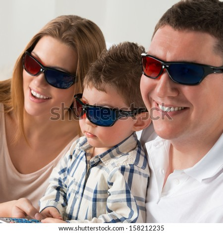 Family laughing while watching television together in the living-room wearing 3d glasses - stock photo
