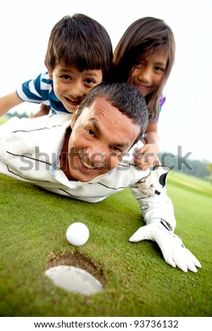 Family laying on the golf course next to the whole - stock photo
