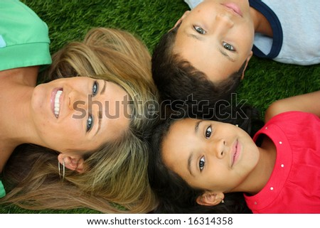 Family Laying Together Outside In The Grass