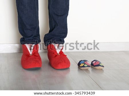 Family legs feet standing together, woman legs and small baby shoes on light background, conceptual photo of family and maternity, pregnancy fragment, maternity - stock photo