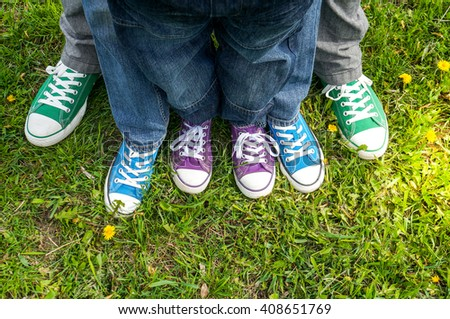 Family legs standing on green grass having fun outdoors in spring park  - stock photo