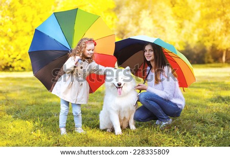 Family, leisure, weather and people concept - mother with child and dog walks with umbrellas outdoors in autumn day - stock photo