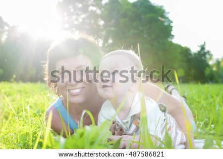 Family Life Concepts and Ideas. Caucasian Brunette Mother with Her Toddler Son Spending Time Together Outdoors Embraced in Park.Horizontal Shot