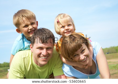 family lifestyle portrait of a mum and dad with their children having good time on the green grass - stock photo